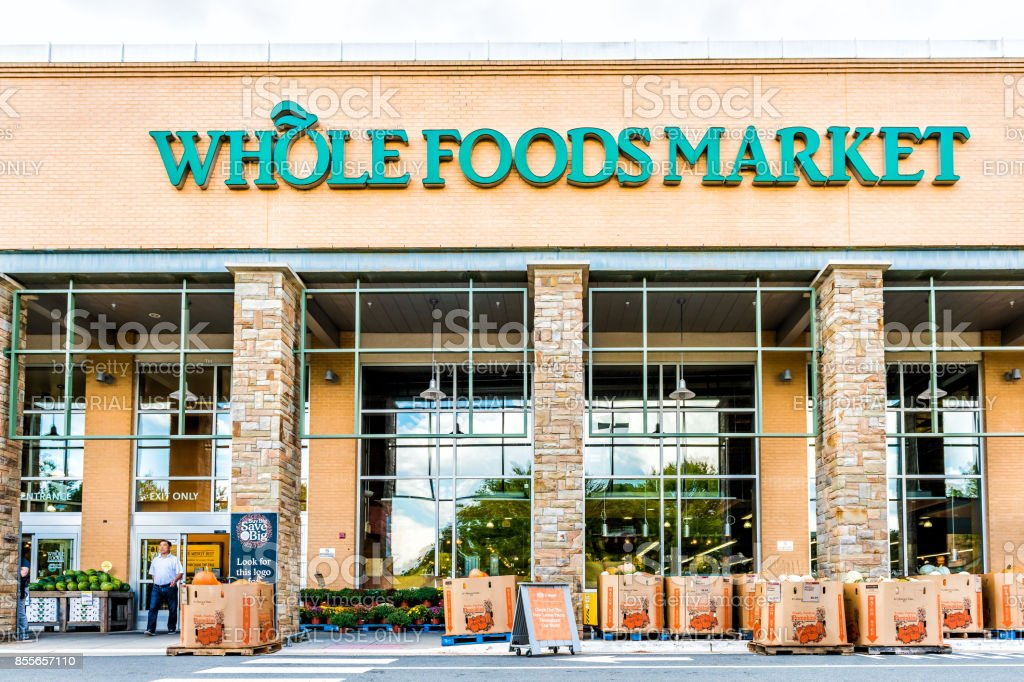 Green Whole Foods Market grocery store sign on exterior building in city in Virginia with people walking and autumn displays of pumpkins for Halloween stock photo