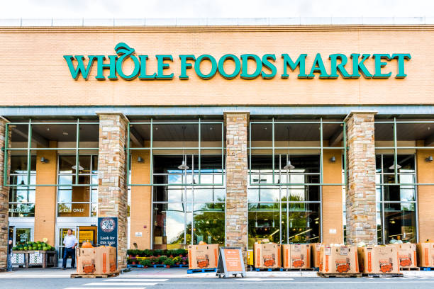 green whole foods market grocery store sign on exterior building in city in virginia with people walking and autumn displays of pumpkins for halloween - food logo stock photos and pictures