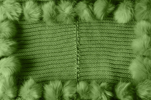 Green winter textile background with copy space and a frame with fluffy tassels