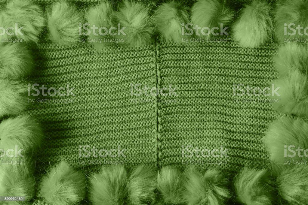 Green winter textile background with copy space and a frame with fluffy tassels stock photo