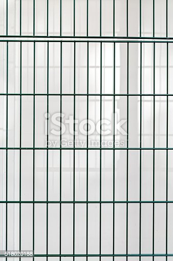 istock Green wire netting fence before white wall background 518020188