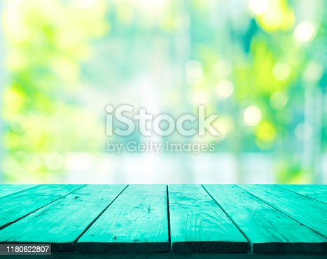 885452818istockphoto Green wood table top on blur abstract green garden from window view 1180622807