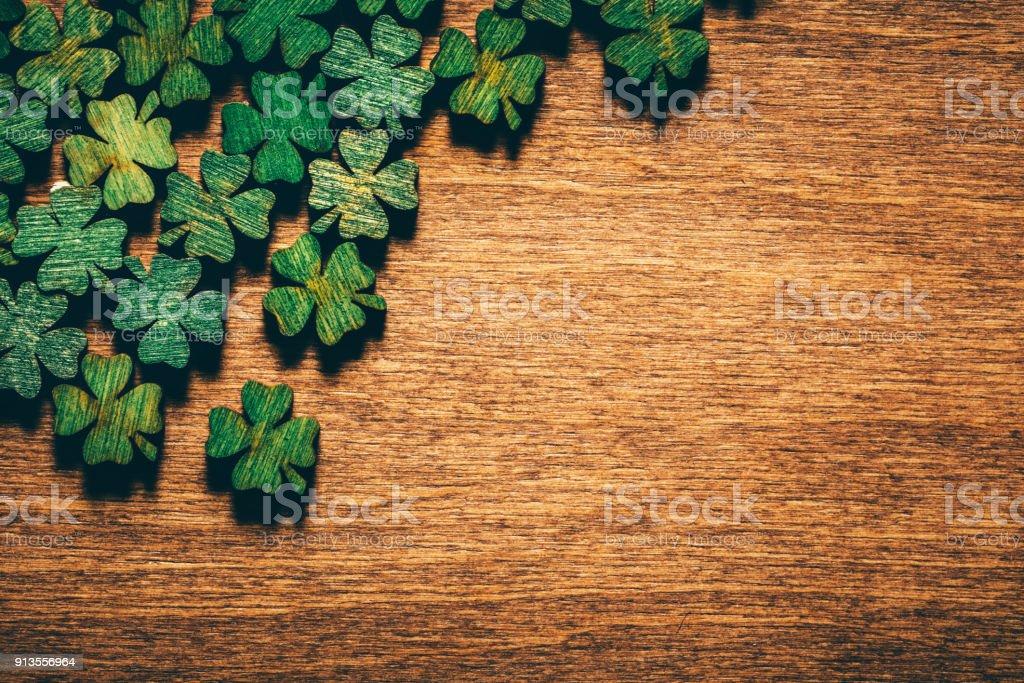 Tréboles de cuatro hojas madera verde en el tablero de madera - foto de stock