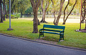 Green wooden long chair beside road in public garden with sunflare