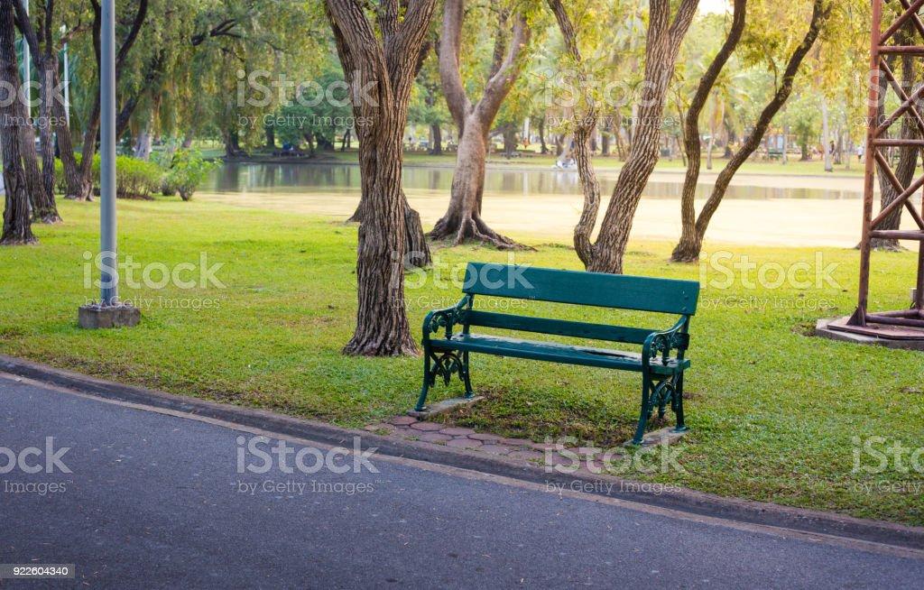 Chaise longue en bois verte à côté de la route dans un jardin public avec sunflare - Photo