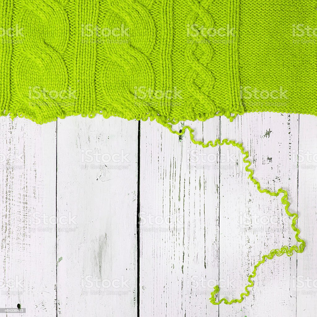 Green woollen knot unraveling on wood stock photo