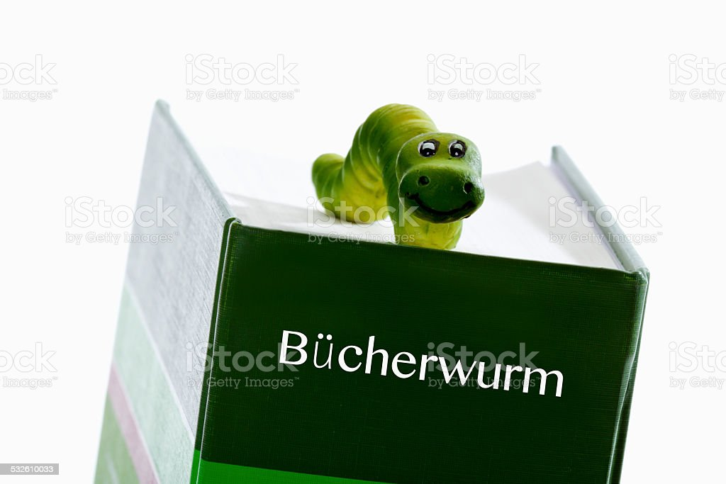 Green worm figure on book stock photo