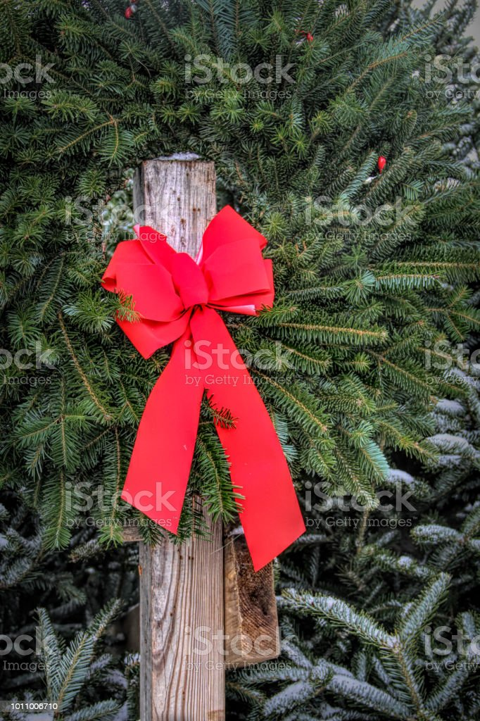 A bright green Christmas Wreath with a red bow is hung for display on...