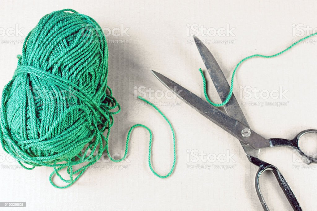 Green yarn with old scissors and only yarn colored stock photo