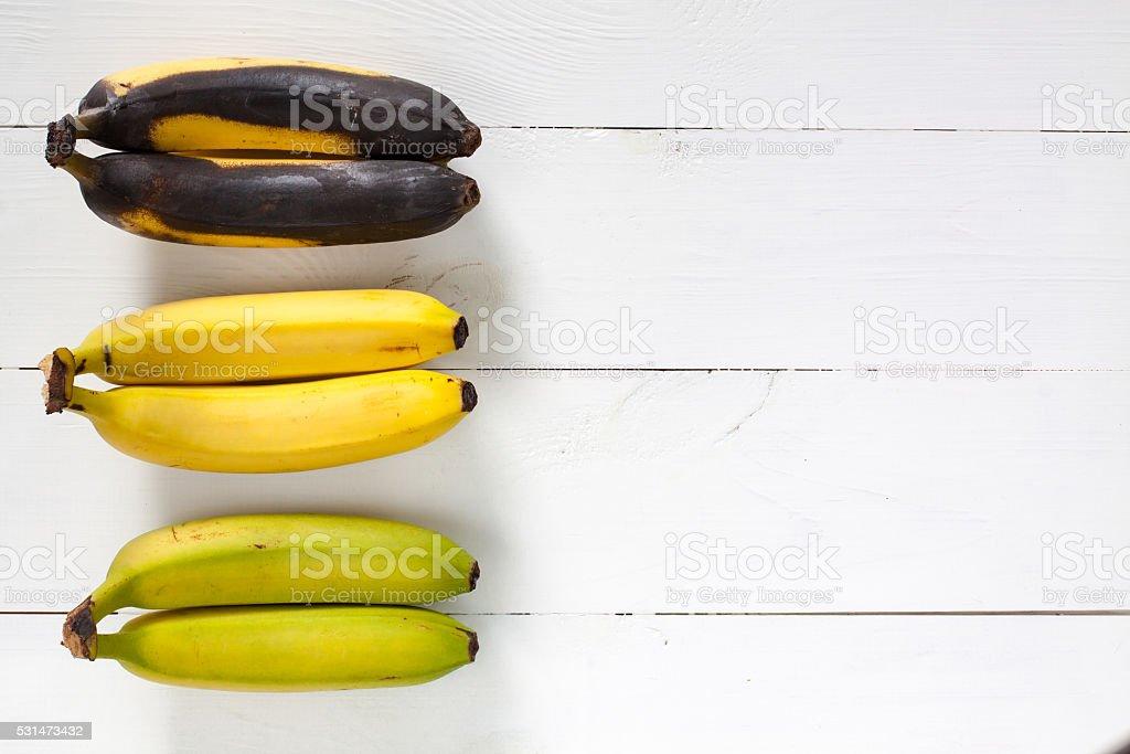 Green, yellow and black bananas. stock photo
