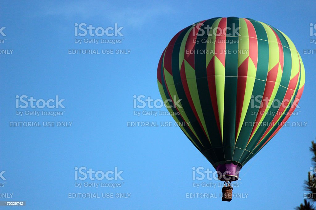 Green, Yellow, and Red Striped Hot Air Balloon in Sky stock photo