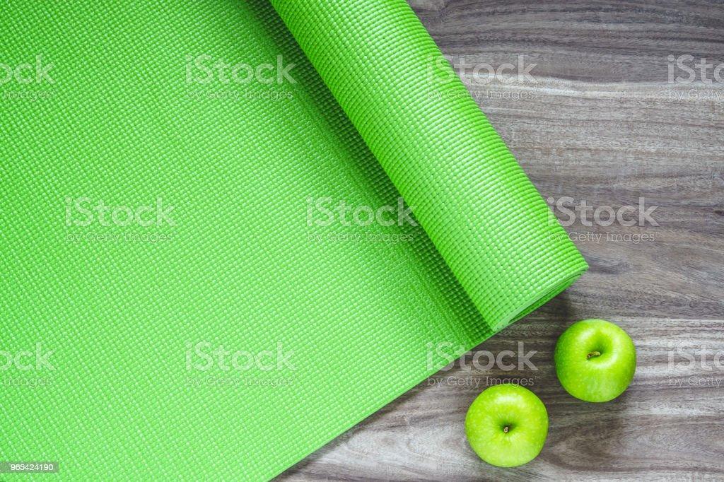 Tapis d'yoga vert sur un fond en bois avec des pommes vertes, vue du dessus avec l'espace de la copie. Concept de mode de vie sain actif de fond. - Photo de Accessoire libre de droits