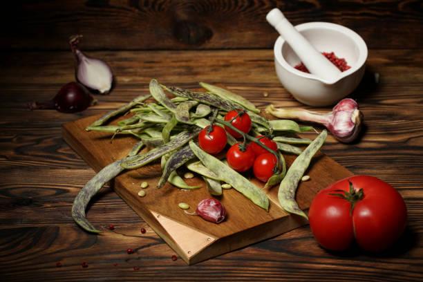 Frijoles verdes y tomates cherry en una tabla de madera sobre una mesa rústica. - foto de stock