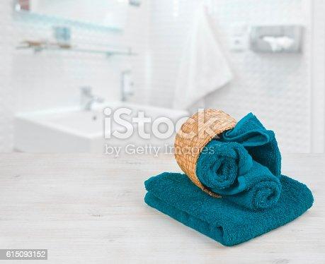 istock Green-blue folded towels in wicker basket over defocused bathroom 615093152