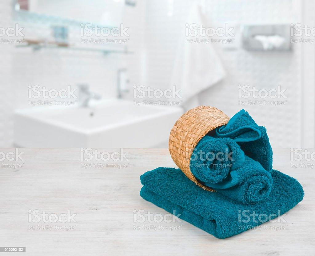 Green-blue folded towels in wicker basket over defocused bathroom stock photo