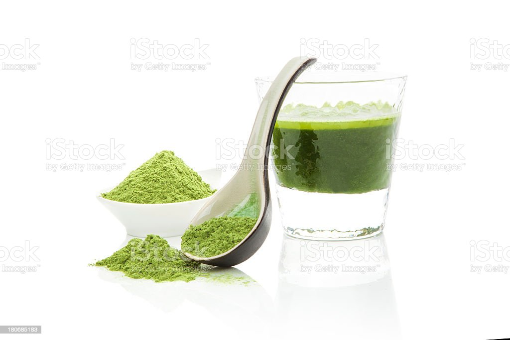 Green-colored food supplements in powder form and in water stock photo