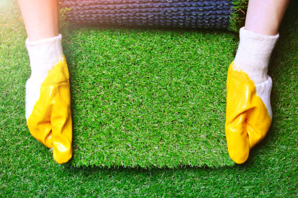 Greenering with an artificial grass background. Landscape designer holds a roll of an artificial turf in his hands. Image with a copy space. Greenering with an artificial grass background. Landscape designer holds a roll of an artificial turf in his hands. Image with a copy space. imitation stock pictures, royalty-free photos & images