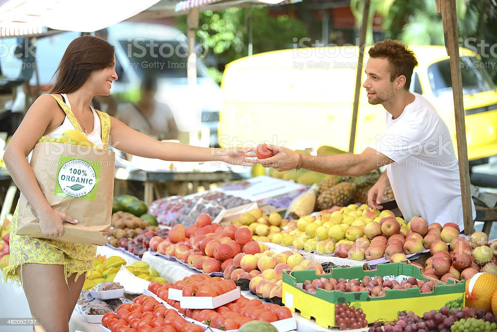 Greengrocer handing out a fruit to a consumer. stock photo