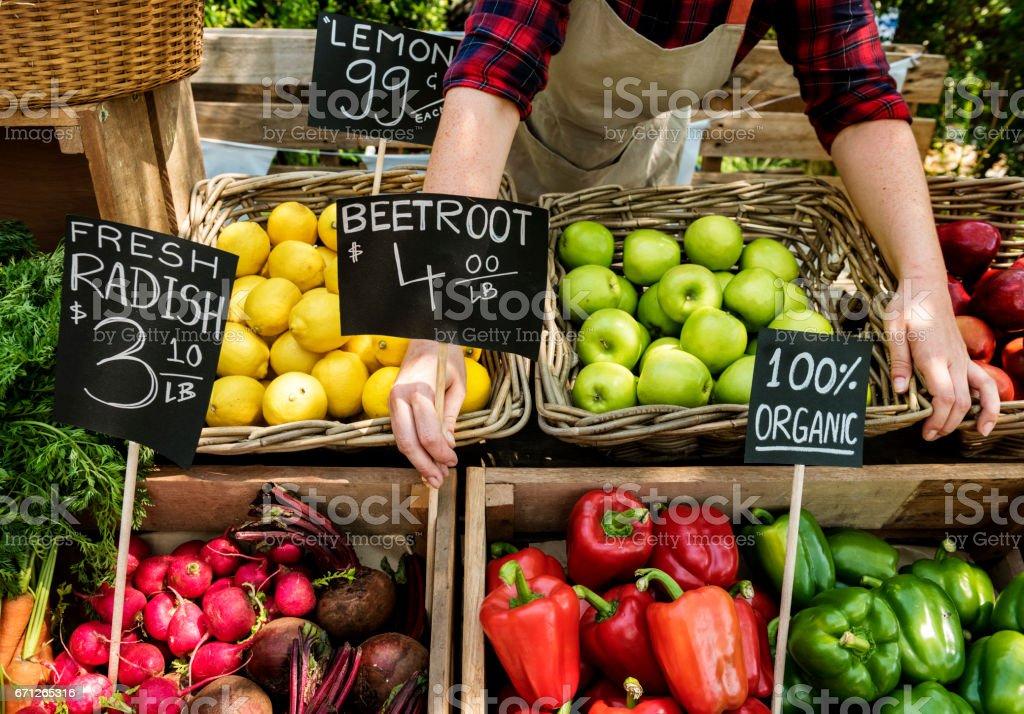 Greengrocer preparing organic fresh agricultural product at farmer market stock photo
