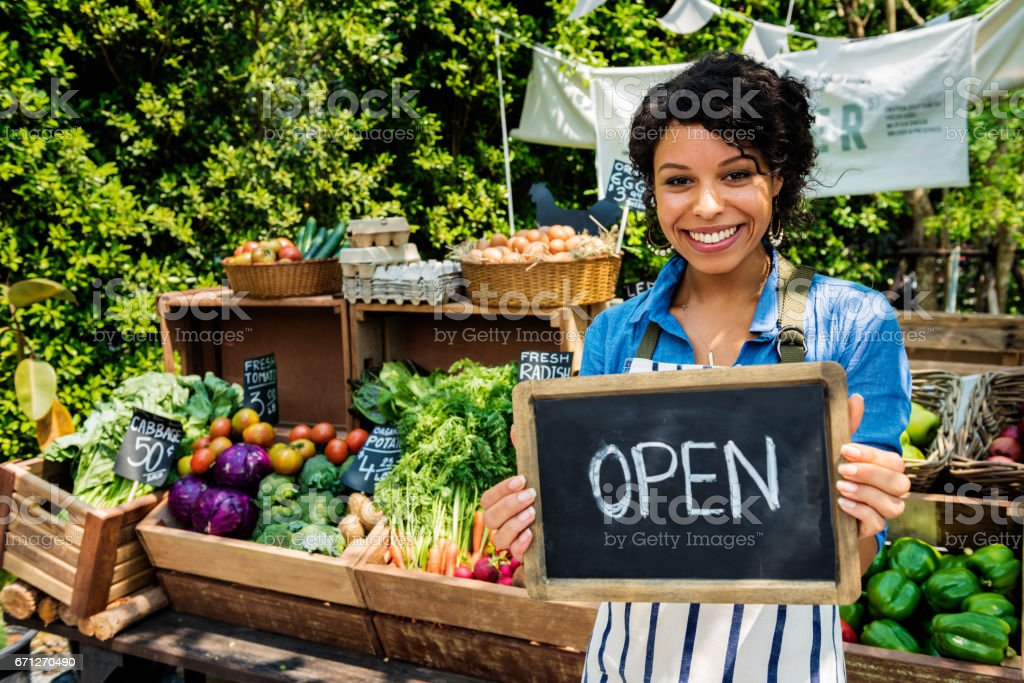Greengrocer selling organic fresh agricultural product at farmer market stock photo
