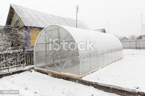 the greenhouse from plastic is located on the earth and covered by falling snow