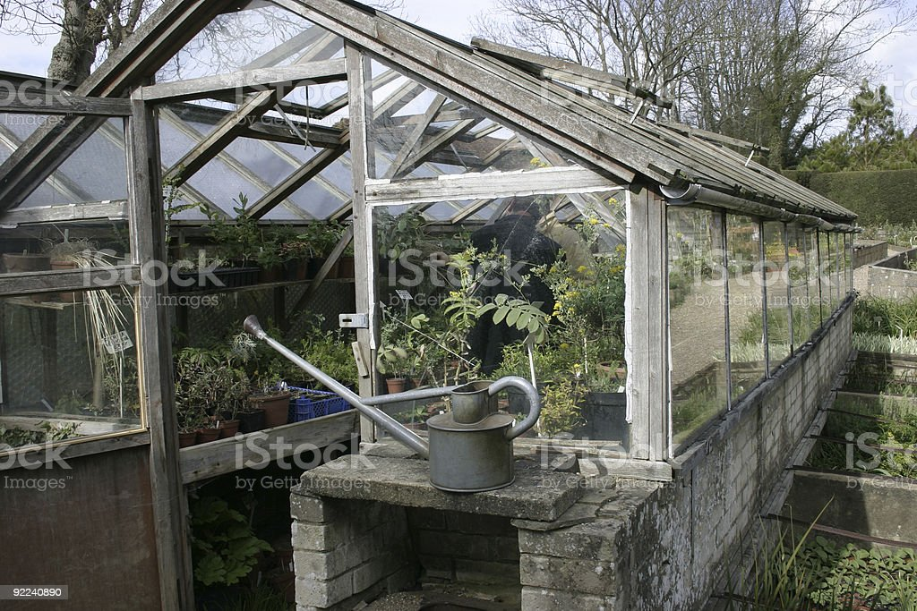 Greenhouse and watering can royalty-free stock photo