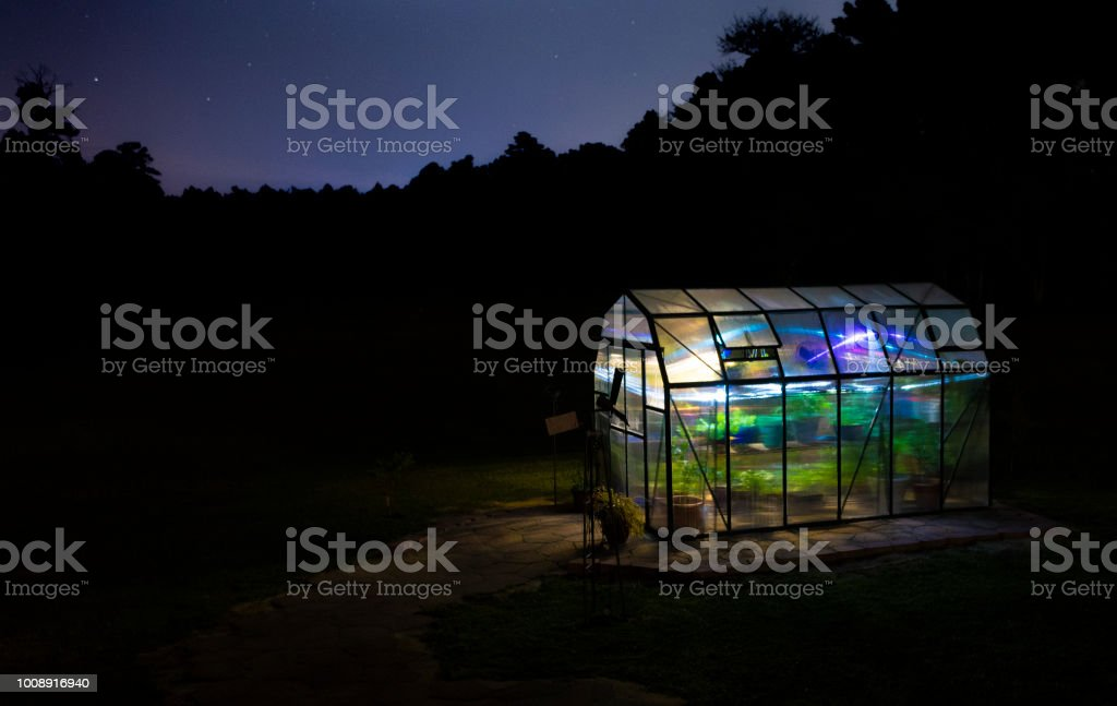 Greenhouse lighted with stars behind stock photo