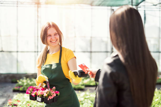 greenhouse workers selling pottered flowers. contactless card payment. - paying with card contactless imagens e fotografias de stock