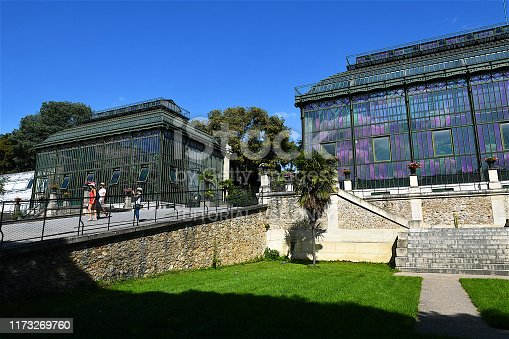 Paris, France-08 19 2019: large Art Deco winter garden, greenhouses display regional plants, not native to France.The Nouvelle Calédonie's Hothouse (on the right) was built between 1834–36 by Charles Rohault de Fleury, is an early example of French glass and metal architecture.
