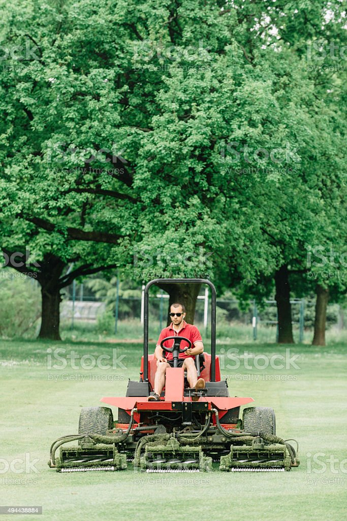 Greenkeeper, mowing fairway at a golf course stock photo