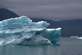 blue iceberg with lightblue spots inside of it and also with dramatic mood of the sky in the atlantic ocean