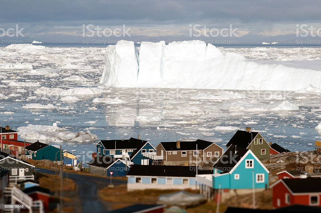 Greenland glacier glaciers houses ocean small town burg sky stock photo