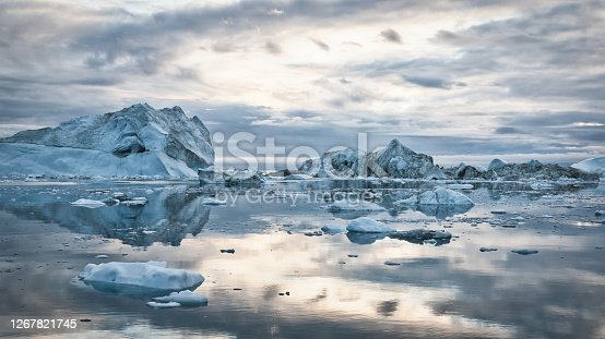 Greenland Arctic Icebergs Sunset Twilight Panorama. Large arctic Iceberg drifting on the polar waters under moody sunset skyscape, cloudscape mirroring in the calm water. Arctic Ocean, Illulissat, Greenland, Denmark, North Polar Region