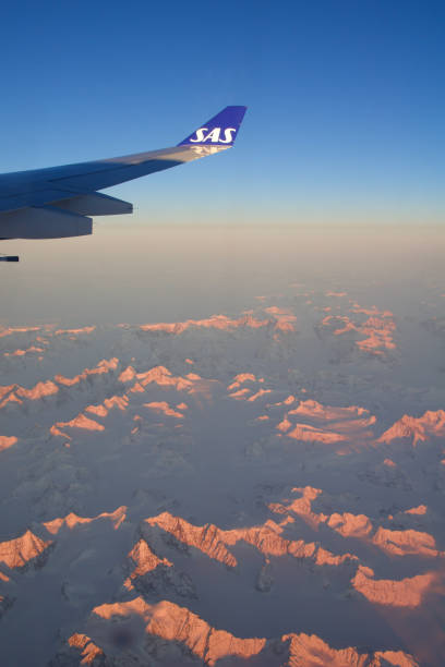 Greenland view from airplane, frozen mountains or glaciers with wing view stock photo