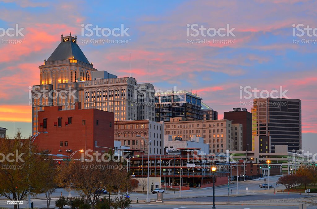 Greensboro skyline with clouds at sunset Greensboro skyline with pink, orange, and yellow at sunset. 2015 Stock Photo