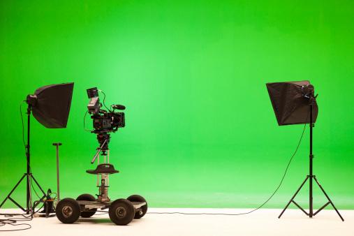 Professional digital camera at a chroma key studio setup.