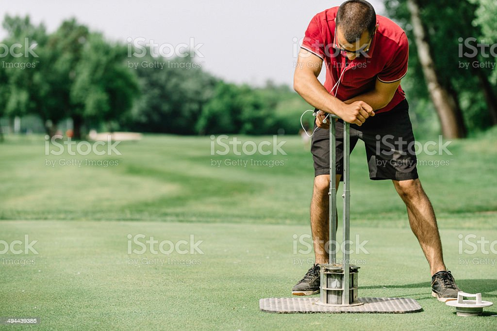 Greenskeeper cutting a golf hole, preparing course stock photo