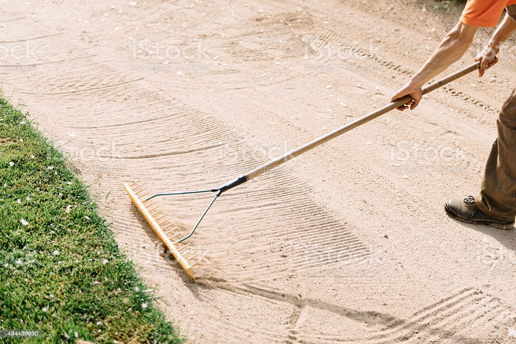 Greenskeeper maintaining golf course, racking sand stock photo