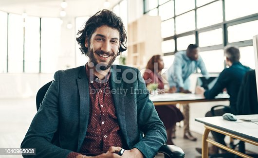 Portrait of a young businessman sitting in a modern office with his colleagues working in the background