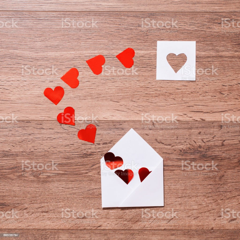 Greeting card. Conceptual photography. Wedding invitation card. Valentine day. Red hearts in envelope on wooden background. Flat lay, top view, copyspace royalty-free stock photo