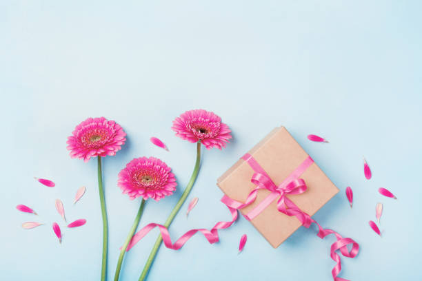 greeting card for birthday, woman or mothers day. spring composition with pink flowers and gift box on blue table top view. - welcome march stock photos and pictures