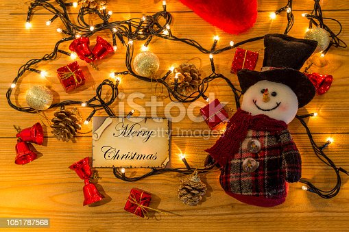 istock Greeting card for new year or christmas with snowman and christmas decors, lights top view 1051787568