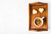 Heart-shaped biscuits and coffee on a wooden tray, top view. Romantic breakfast. Greeting card for St. Valentine's Day.