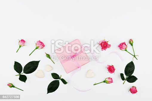 825251738istockphoto Greeting card from gift box and pink roses. Flat lay. 642727336
