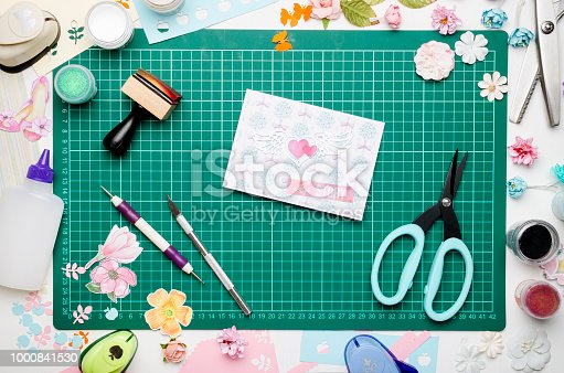 greeting card on green cutting mat, scrapbooking tools and materials, top view, no hands