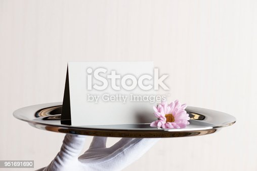 Hotel servant is holding a empty greeting card on a silver tray with a pink flower.