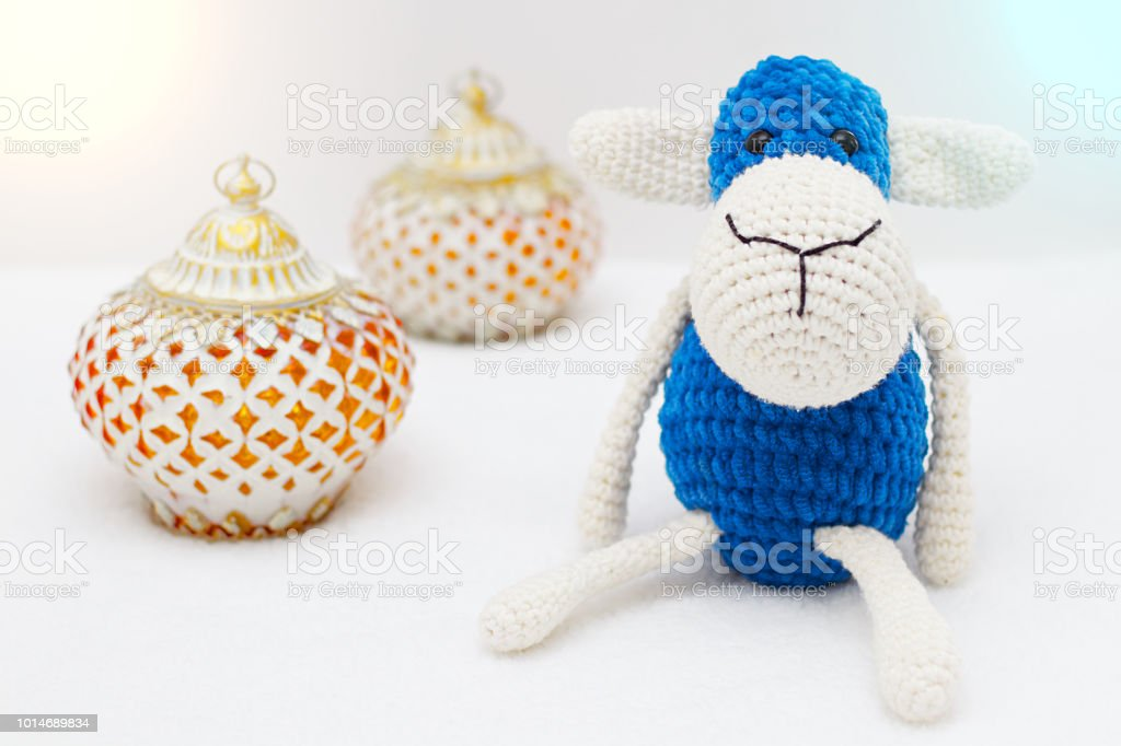 Greeting card on white background. Eid Al Adha sacrifice festival, Islamic Arabic candle and blue sheep. stock photo