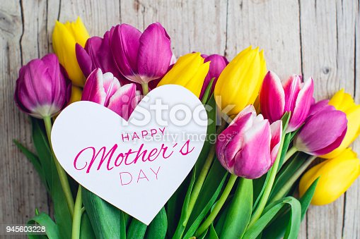 istock Greeting card - Pink and yellow tulips on a wooden background 945603228