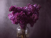 istock Greeting card with a beautiful purple lilac bouquet in low key. Spring seasonal background. 1286763656