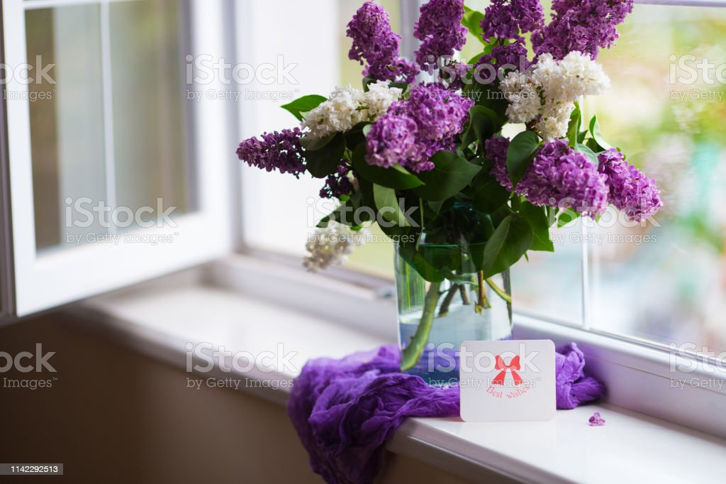 Greeting card with best wishes and tender bouquet of beautiful lilac in glass vase near window in daylight. stock photo
